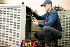 HVAC service technician working on outdoor air conditioner unit.